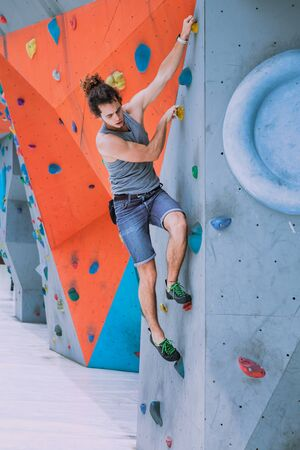 Urban concept of man with curly long hair, tied in a ponytail, is training at the city artificial red and blue climbing wall using talcum powder, wearing a bag for climbing without insurance equipment