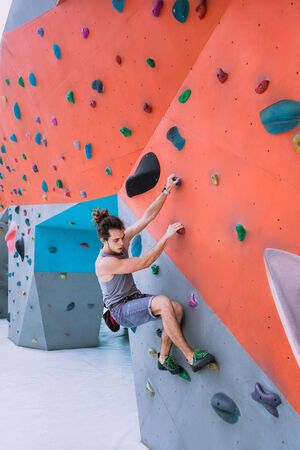 Urban concept of man with curly long hair, tied in a ponytail, is training at the city artificial red and blue climbing wall using talcum powder, wearing a bag for climbing without insurance equipment 版權商用圖片 - 146104509