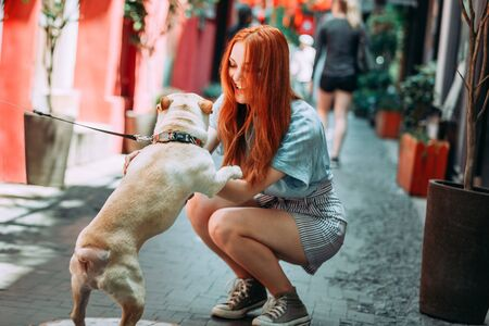 Young red hair woman playing with white bulldog dog outdoors in the street in Tianzifan district 版權商用圖片 - 146104511
