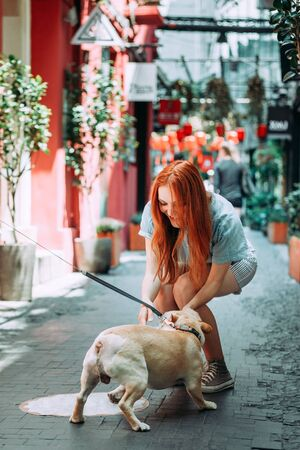 Young red hair woman playing with white bulldog dog outdoors in the street in Tianzifan district 版權商用圖片