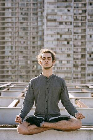Meditating young european man sitting with eyes closed in lotus pose croosed legs on blurry urban residential building city background. Urban yoga concept. Relaxation in city life