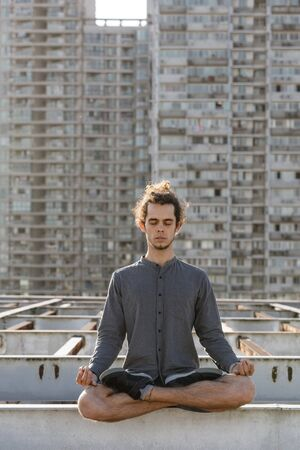 Meditating young european man sitting with eyes closed in lotus pose croosed legs on blurry urban residential building city background. Urban yoga concept. Relaxation in city life 版權商用圖片 - 146104521