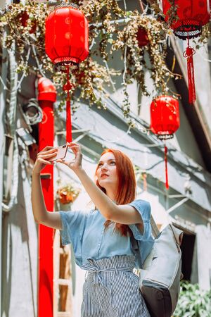 Red hair tourist uses mobile phone for picture with smartphone of Yuyuan Garden street with red lanterns in Shanghai, china. Asia tourism travel. People taking photos during vacation lifestyle concept