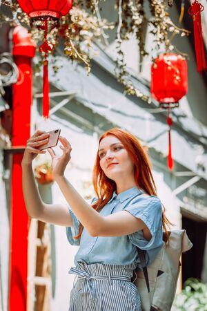Red hair tourist uses mobile phone for picture with smartphone of Yuyuan Garden street with red lanterns in Shanghai, china. Asia tourism travel. People taking photos during vacation lifestyle concept Reklamní fotografie - 146104654