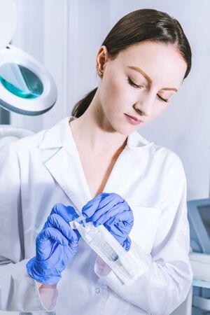 Sterile medicine equipment. Doctor wearing white medical uniform and sterile blue gloves opening sterile medical needle syringe. 版權商用圖片 - 146104657