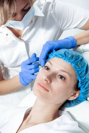 doctor cosmetologist makes Rejuvenating Biorevitalization facial injections procedure for tightening and smoothing wrinkles on face skin of female mid-age in beauty salon clinic. Cosmetology skin care Reklamní fotografie - 149099887