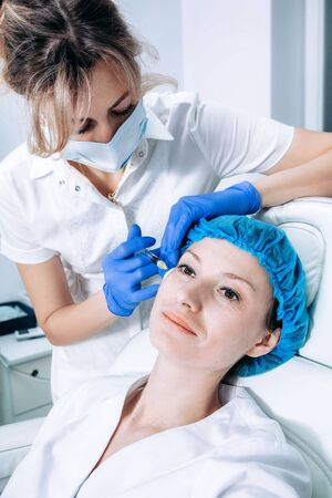 doctor cosmetologist makes Rejuvenating Biorevitalization facial injections procedure for tightening and smoothing wrinkles on face skin of female mid-age in beauty salon clinic. Cosmetology skin care Reklamní fotografie - 147503392