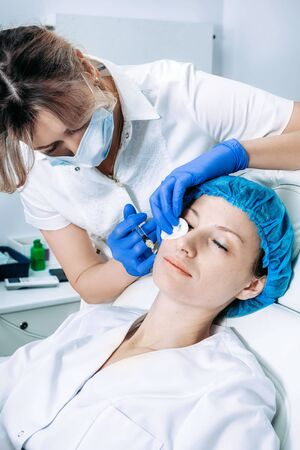 doctor cosmetologist makes Rejuvenating Biorevitalization facial injections procedure for tightening and smoothing wrinkles on face skin of female mid-age in beauty salon clinic. Cosmetology skin care 版權商用圖片 - 147502954