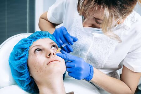 doctor cosmetologist makes Rejuvenating Biorevitalization facial injections procedure for tightening and smoothing wrinkles on face skin of female mid-age in beauty salon clinic. Cosmetology skin care Reklamní fotografie - 147502992