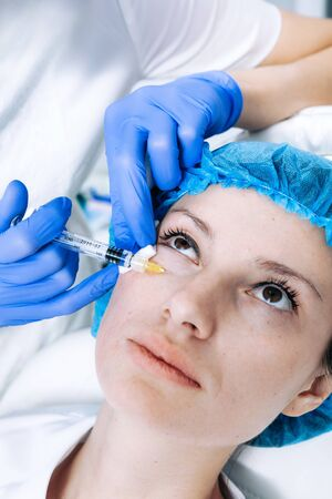 doctor cosmetologist makes Rejuvenating Biorevitalization facial injections procedure for tightening and smoothing wrinkles on face skin of female mid-age in beauty salon clinic. Cosmetology skin care Reklamní fotografie - 149099913