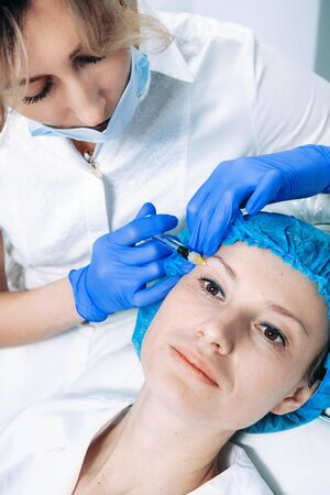 doctor cosmetologist makes Rejuvenating Biorevitalization facial injections procedure for tightening and smoothing wrinkles on face skin of female mid-age in beauty salon clinic. Cosmetology skin care Reklamní fotografie - 149099915