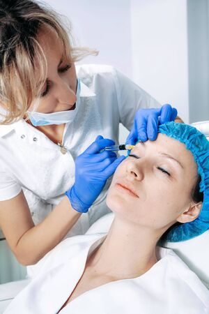 doctor cosmetologist makes Rejuvenating Biorevitalization facial injections procedure for tightening and smoothing wrinkles on face skin of female mid-age in beauty salon clinic. Cosmetology skin care