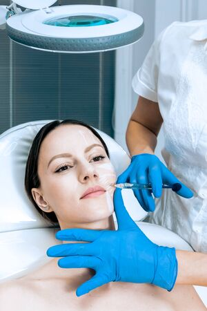 doctor cosmetologist makes Rejuvenating Biorevitalization facial injections procedure for tightening and smoothing wrinkles on face skin of female mid-age in beauty salon clinic. Cosmetology skin care Reklamní fotografie - 147568271