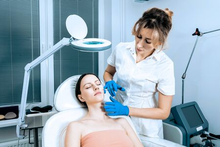 doctor cosmetologist makes Rejuvenating Biorevitalization facial injections procedure for tightening and smoothing wrinkles on face skin of female mid-age in beauty salon clinic. Cosmetology skin care 版權商用圖片 - 147507066