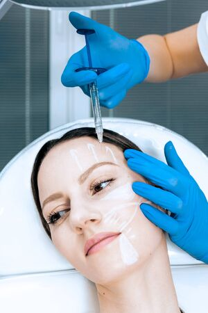 doctor cosmetologist makes Rejuvenating Biorevitalization facial injections procedure for tightening and smoothing wrinkles on face skin of female mid-age in beauty salon clinic. Cosmetology skin care Reklamní fotografie - 147507374