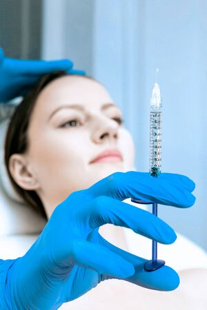 close up of a young beautiful woman getting fillers injection in her face receiving beauty facial treatment at the clinic plastic surgery fillers syringe injector sterile profession procedure..