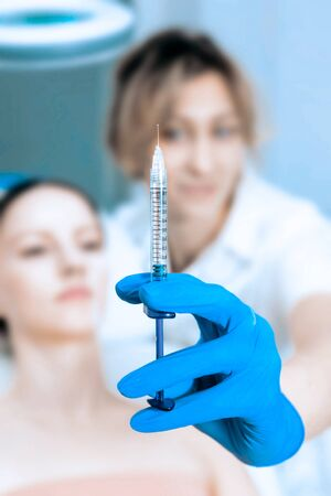 close up of a young beautiful woman getting fillers injection in her face receiving beauty facial treatment at the clinic plastic surgery fillers syringe injector sterile profession procedure.. Reklamní fotografie - 149099960