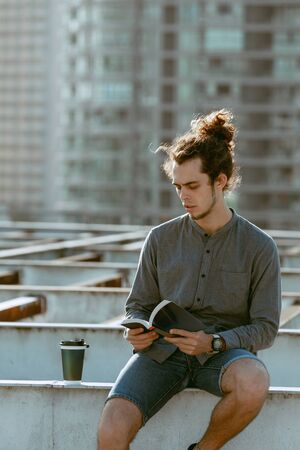Man sitting on roof and reading book, drinking coffee, tea, drink in paper cup in grey shirt, blue jeans shorts, curly hair collected in high ponytale . Background cityscapes. Urban lifestyle concept