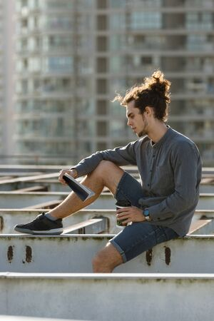 Man sitting on roof and reading book, drinking coffee, tea, drink in paper cup in grey shirt, blue jeans shorts, curly hair collected in high ponytale . Background cityscapes. Urban lifestyle concept Reklamní fotografie - 149099965