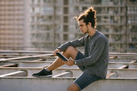 Man sitting on roof and reading book, drinking coffee, tea, drink in paper cup in grey shirt, blue jeans shorts, curly hair collected in high ponytale . Background cityscapes. Urban lifestyle concept Reklamní fotografie - 149099967