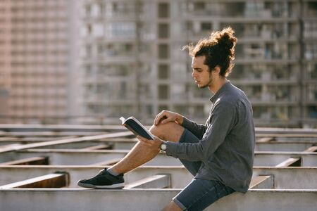 Man sitting on roof and reading book, drinking coffee, tea, drink in paper cup in grey shirt, blue jeans shorts, curly hair collected in high ponytale . Background cityscapes. Urban lifestyle concept Reklamní fotografie - 149099977