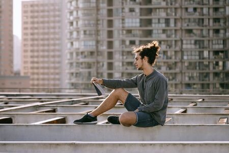 Man sitting on roof and reading book, drinking coffee, tea, drink in paper cup in grey shirt, blue jeans shorts, curly hair collected in high ponytale . Background cityscapes. Urban lifestyle concept Reklamní fotografie - 149100096
