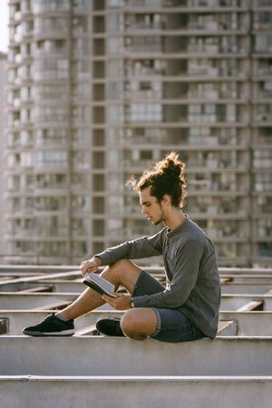 Man sitting on roof and reading book, drinking coffee, tea, drink in paper cup in grey shirt, blue jeans shorts, curly hair collected in high ponytale . Background cityscapes. Urban lifestyle concept Reklamní fotografie - 149100097
