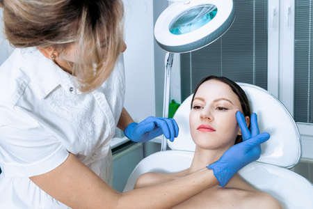 Young woman at beauty clinic cosmetology service sitting on medical chair while female doctor wearing gloves holding her face examining skin with mirror concentrated close-up. Reklamní fotografie - 156266192