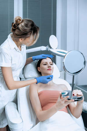 Young woman at beauty clinic cosmetology service sitting on medical chair while female doctor wearing gloves holding her face examining skin with mirror concentrated close-up