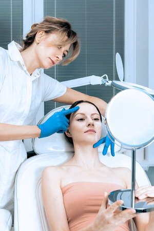 Young woman at beauty clinic cosmetology service sitting on medical chair while female doctor wearing gloves holding her face examining skin with mirror concentrated close-up.