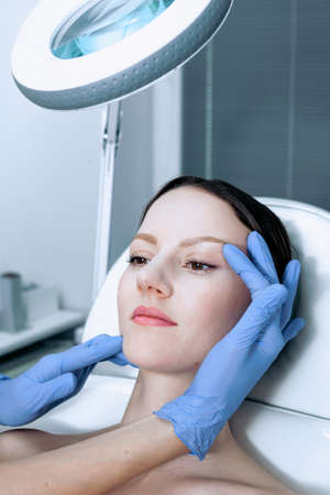 Face skin check before plastic surgery. Beautician touching woman face wearing blue medical gloves Reklamní fotografie - 156264231