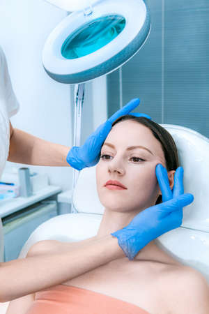 Face skin check before plastic surgery. Beautician touching woman face wearing blue medical gloves Reklamní fotografie - 156264233