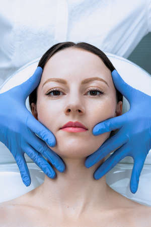 Face skin check before plastic surgery. Beautician touching woman face wearing blue medical gloves Reklamní fotografie