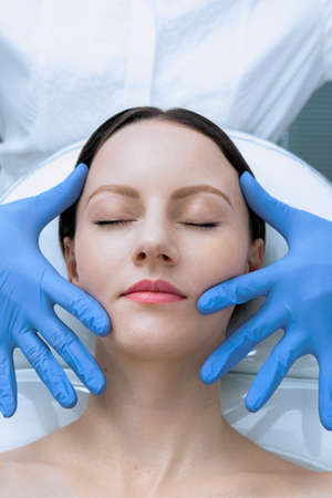 Face skin check before plastic surgery. Beautician touching woman face wearing blue medical gloves 版權商用圖片