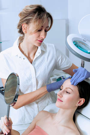 Young woman at beauty clinic cosmetology service sitting on medical chair while female doctor wearing gloves holding her face examining skin with mirror concentrated close-up. Reklamní fotografie - 155529168