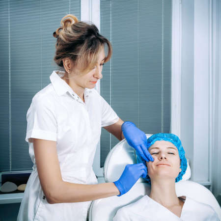 Cosmetologist is applying cream with anesthesia on patient's face, portrait closeup view. Preparing skin for biorevitalization procedure in cosmetology. Woman in beauty clinic with doctor beautician. Reklamní fotografie - 155428516