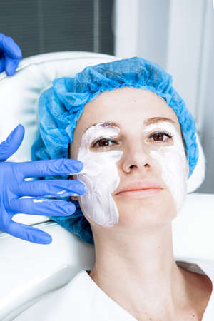 Cosmetologist is applying cream with anesthesia on patient's face, portrait closeup view. Preparing skin for biorevitalization procedure in cosmetology. Woman in beauty clinic with doctor beautician. Reklamní fotografie - 155428517