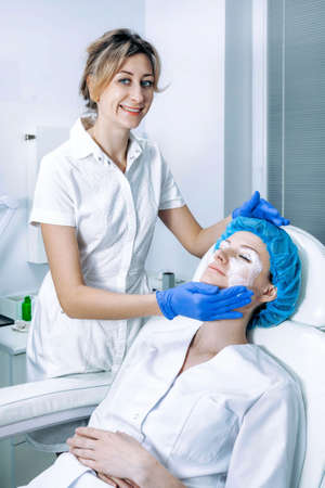 Cosmetologist is applying cream with anesthesia on patient's face, portrait closeup view. Preparing skin for biorevitalization procedure in cosmetology. Woman in beauty clinic with doctor beautician.