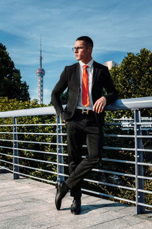 Man dressed in a black suit, red tie, a handsome, sexy, middle age businessman standing in the front of a business district. Portrait of Businessman. Financial white colar lifestyle concept Reklamní fotografie