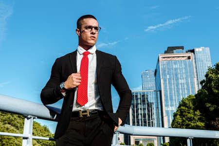Man dressed in a black suit, red tie, a handsome, sexy, middle age businessman standing in the front of a business district. Portrait of Businessman. Financial white colar lifestyle concept 版權商用圖片