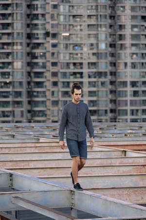 Man walking on the rooftop, wearing casual, curly hair collected in the pony tail. Background of residential buliding. Urban rooftopper extreme lifestyle, cityscape, abandoned atmosphere 版權商用圖片