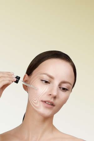 Female applying anti wrinkle serum on face, brown hair gathered in low ponytail, studio beauty shot, yellow isolated background, graphic massage lines visualize effect of skin care product