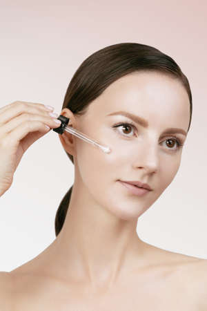 Female applying anti wrinkle serum on face, brown hair gathered in low ponytail, studio beauty shot, light beige isolated background, visualize effect of skin care product
