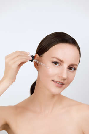 Female applying anti wrinkle serum on face, looks in camera smiling, brown hair gathered in low ponytail, studio beauty shot, white isolated background 版權商用圖片