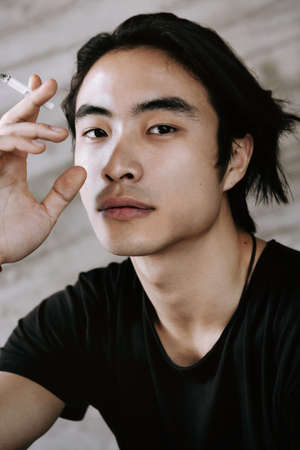 Asian man smoking, lighting the cigarette, long dark haircut, wearing black t-shirt on the grungy background, model test shoot, looking in the camera