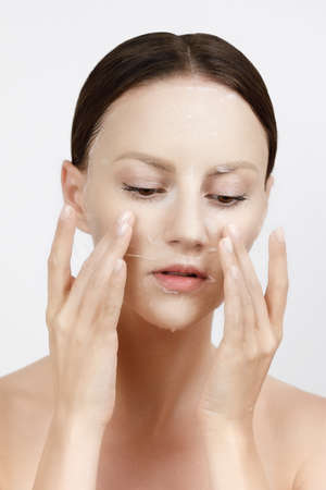 Face Skin Care moisturizing Korean cosmetics concept. Portrait Of Beautiful woman applying nd smoothing White Sheet Mask on Healthy Fresh Skin. Cloth Mask On Facial Skin. High resolution