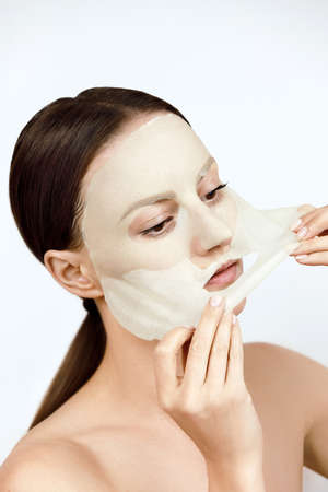 Face Skin Care moisturizing Korean cosmetics concept. Portrait Of Beautiful woman Removing White Sheet Mask From Healthy Fresh Skin. Cloth Mask On Facial Skin. High resolution