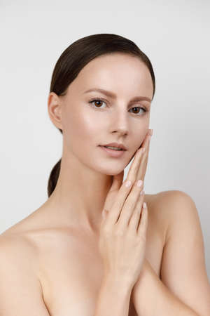 Young woman with beautiful healthy face - isolated on white background, studio hi-end shot, skin care concept. Hands and fingers gently touch facial skin, brown hair parted, gathered in low ponytail