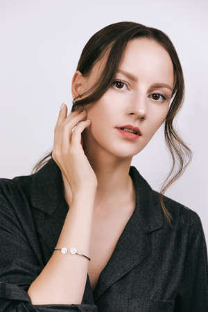 woman portrait wearing gray shirt, air long curtain bangs see-through fringe in retro Korean style. Hand touches face, bracelette on the arm 版權商用圖片