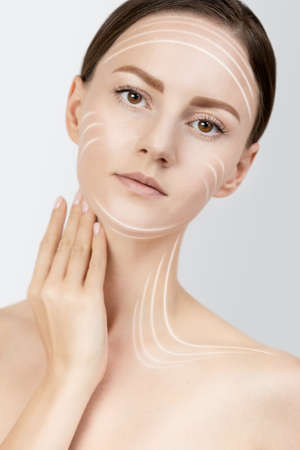 Female applying anti wrinkle serum on skin face, brown hair gathered in a low ponytail, studio beauty shot on a white isolated background, skin care concept